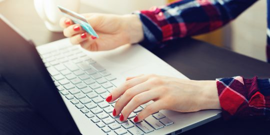Woman using laptop to make online payment with credit card