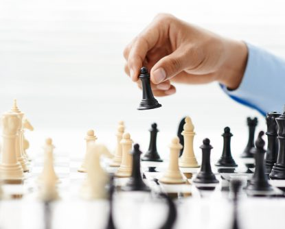 Hand of businessman playing chess