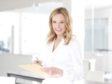 Portrait of a confident middle aged female professional holding a clipboard and making notes while standing at office after business meeting.