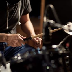 music, people, musical instruments and entertainment concept - male musician playing drums and cymbals at concert or studio