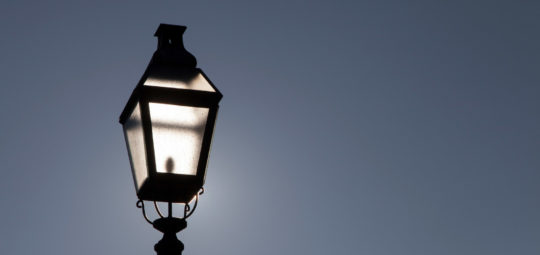 Old street lamp on a background of dramatic dark blue skyBacklig
