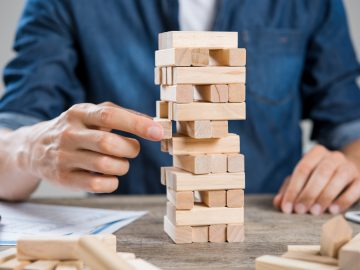Businessman thinking about new challenge. Close up of hand of man taking a piece of building wooden bricks. Businessman trying to find a solution to problem by building with wooden bricks. Risk and strategy concept.
