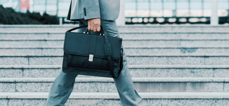 Close-up of businessman with a briefcase running in a city street. Hurrying to work.
