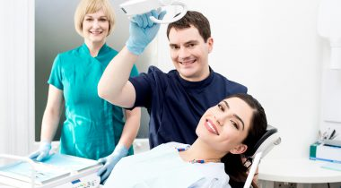 Smiling dentist and assistant with female patient