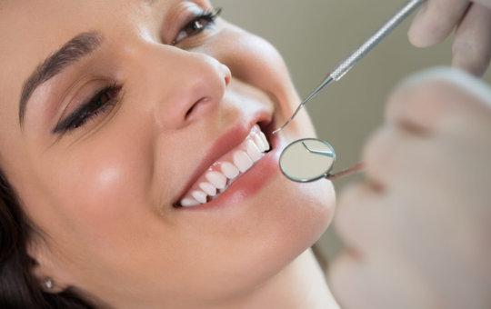 Closeup of dentist examining young woman`s teeth