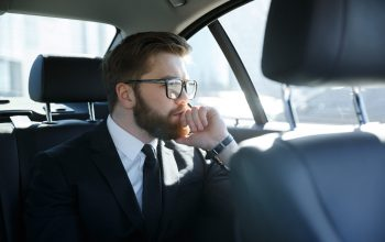 Potrait of a concentrated bearded business man in eyeglasses sitting in the back seat of car
