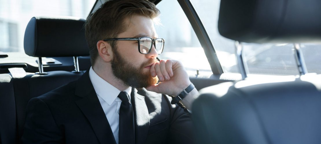 Man in eyeglasses sitting at the back seat of car