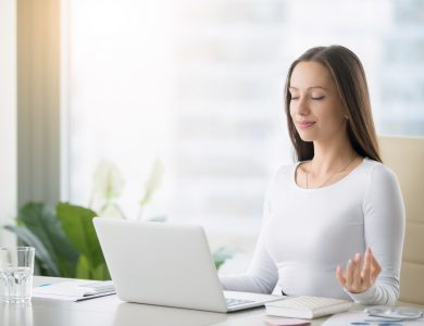 Young woman near the laptop, practicing meditation at the office desk, in front of laptop, online yoga classes, taking a break time for a minute, healing from paperwork and laptop radiation