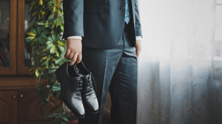 The young man holds shoes.