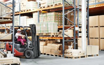 warehouse worker driver in uniform loading cardboxes by forklift stacker loader