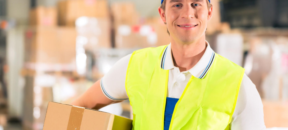 Warehouseman with protective vest and scanner, holds package, he standing at warehouse of freight forwarding company