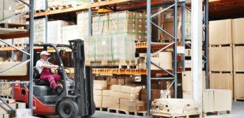 warehouse worker driver in uniform loading cardboxes by forklift stacker loader