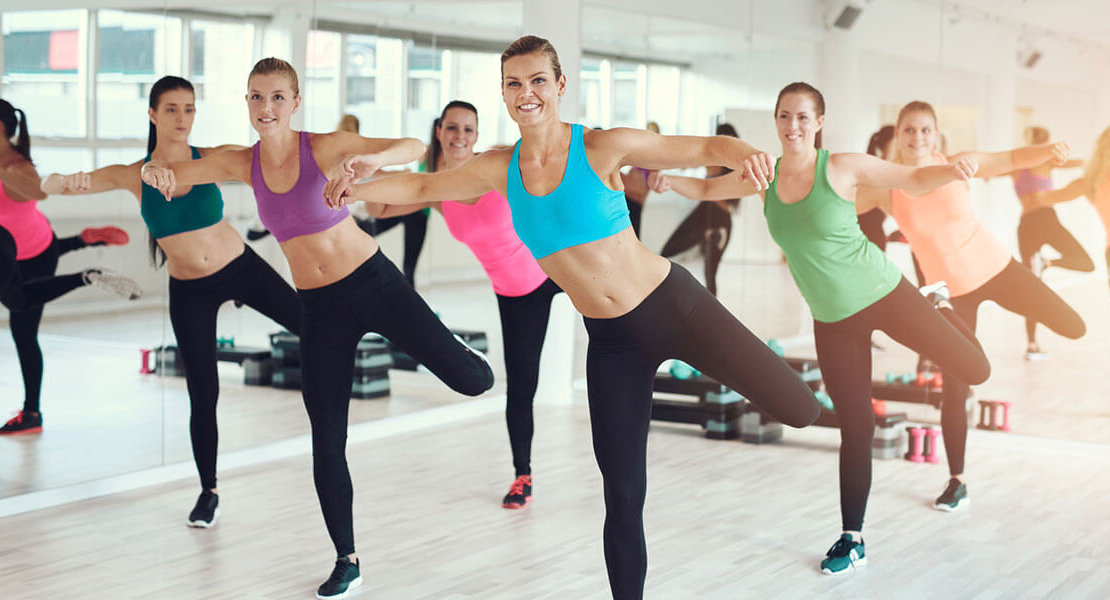Large colorful group of fit young women working out in a gym doing aerobics exercises in a health and fitness concept